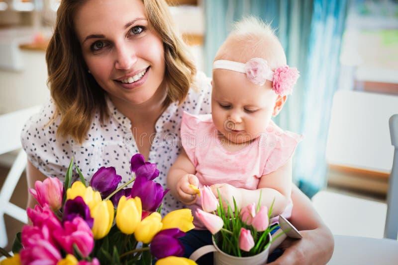 Den lyckliga modern och behandla som ett barn danandegarnering med buketten av tulpan royaltyfri foto