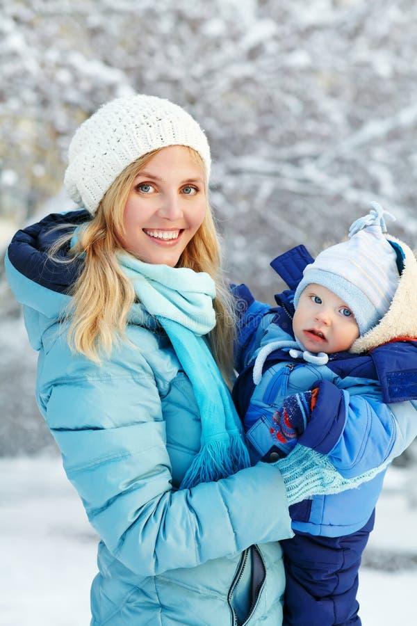 Den lyckliga modern och behandla som ett barn i vinter parkerar arkivbild