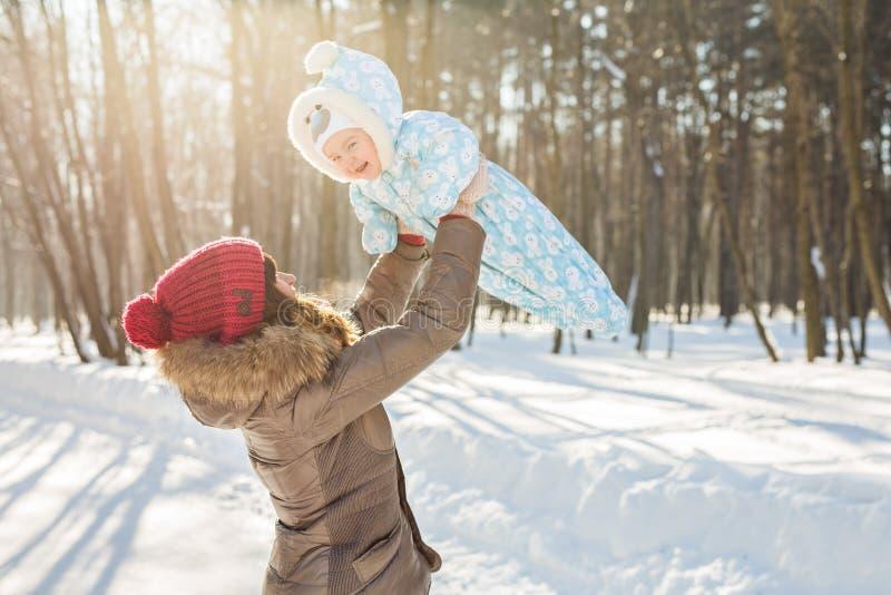 Den lyckliga modern och behandla som ett barn i vinter parkerar arkivfoton