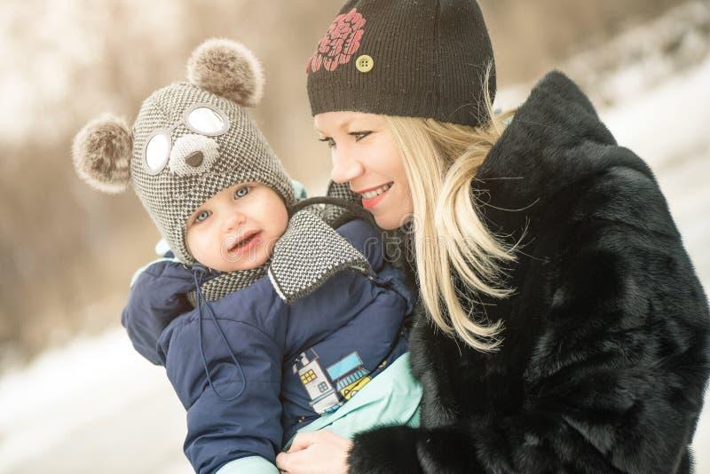 Den lyckliga modern och behandla som ett barn i vinterskog arkivbilder