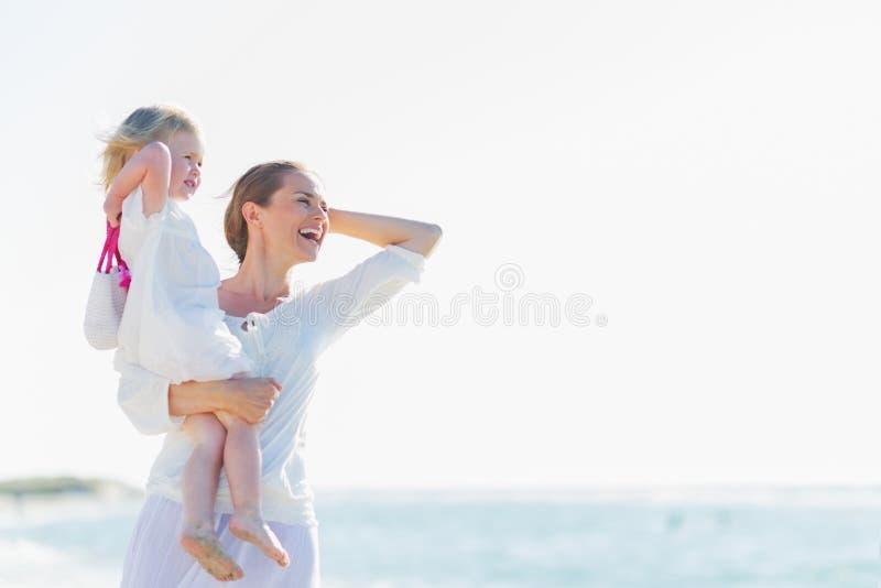 Den lyckliga modern och behandla som ett barn på stranden som ser in i avstånd arkivbild