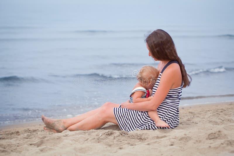 Den lyckliga modern och den lilla dottern går vidare kusten royaltyfri foto