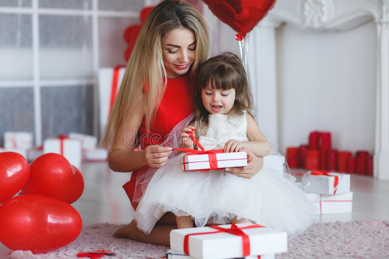 Den lyckliga modern och dottern analyserar gåvor på dag för valentin` s arkivfoton