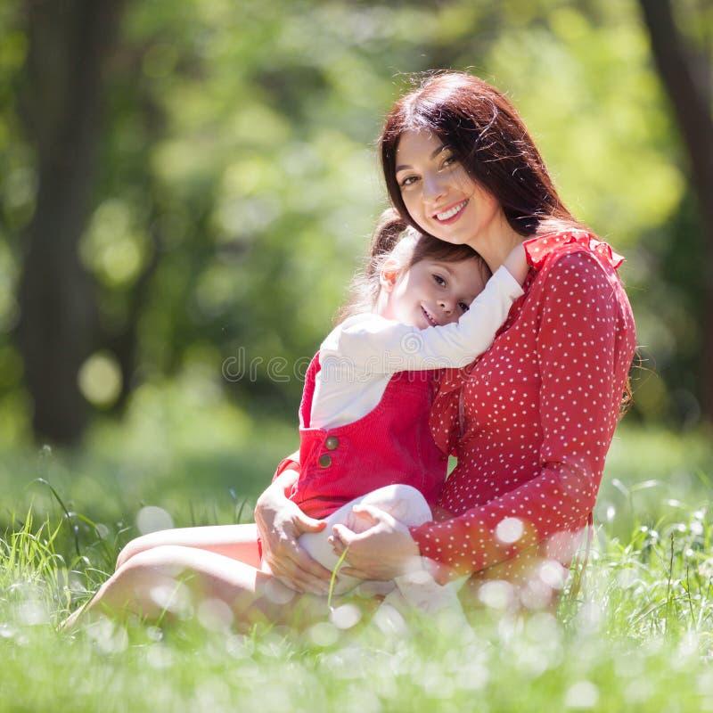 Den lyckliga modern och dottern i sommaren parkerar Sk?nhetnaturplats med utomhus- livsstil f?r familj Lycklig familj som tillsam arkivfoto