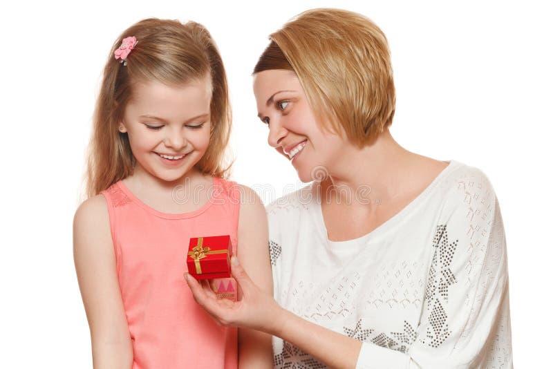 Den lyckliga modern och dottern med gåvaasken, mamma ger en gåva som isoleras på vit bakgrund royaltyfria foton
