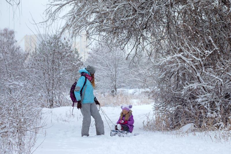 Den lyckliga modern och dottern på en vinter går arkivfoton