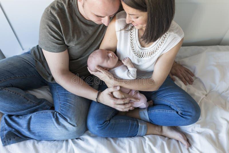 den lyckliga modern och fadern med henne behandla som ett barn flickan hemma Livsstil inomhus och familjförälskelsebegrepp arkivfoto