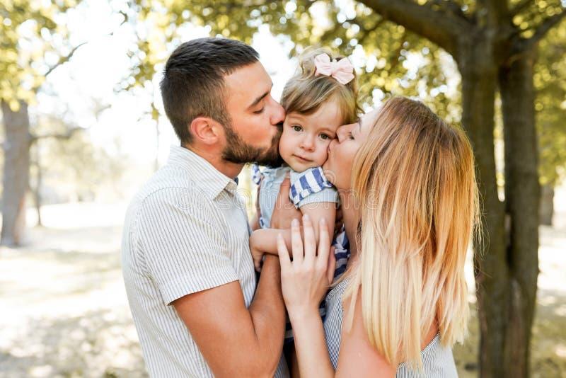 Den lyckliga modern och fadern som kysser den lilla dottern i, parkerar royaltyfri bild