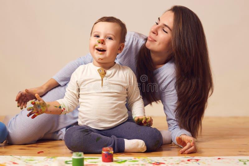 Den lyckliga modern och hennes lilla son med målarfärger på hans iklädda hem- kläder för framsidan sitter på trägolvet i royaltyfria foton