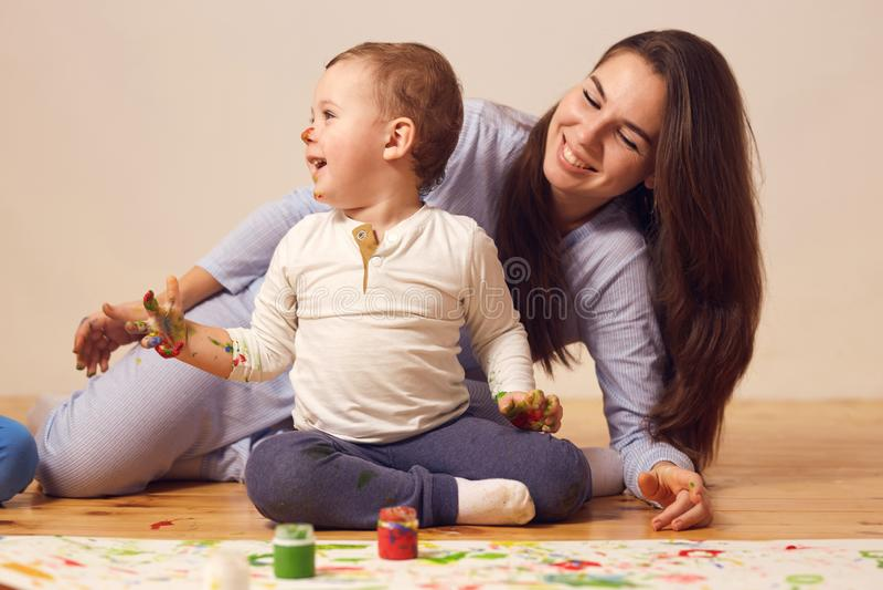 Den lyckliga modern och hennes lilla son med m?larf?rger p? hans ikl?dda hem- kl?der f?r framsidan sitter p? tr?golvet i royaltyfri fotografi