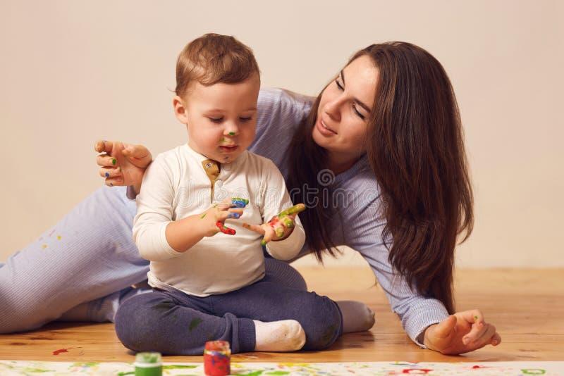 Den lyckliga modern och hennes lilla son med m?larf?rger p? hans ikl?dda hem- kl?der f?r framsidan sitter p? tr?golvet i arkivbilder