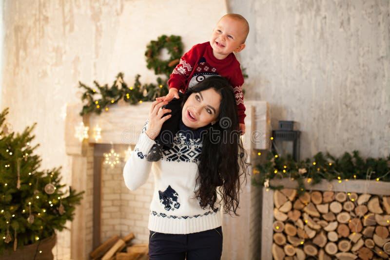 Den lyckliga modern och hennes lilla son spelar på bakgrund av julgranen royaltyfri foto