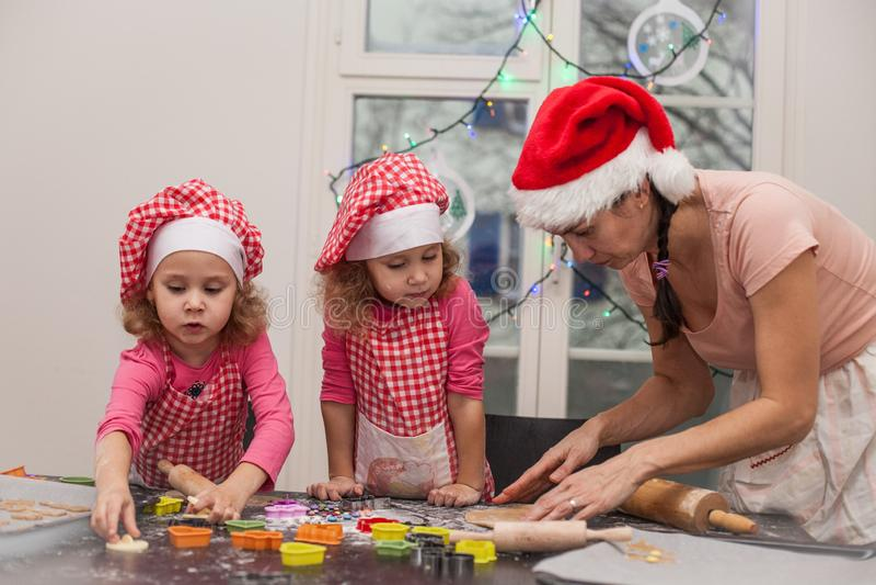Den lyckliga modern och identiska tvilling- döttrar för barn bakar att knåda deg i köket, den unga familjen som förbereder julkak arkivfoton