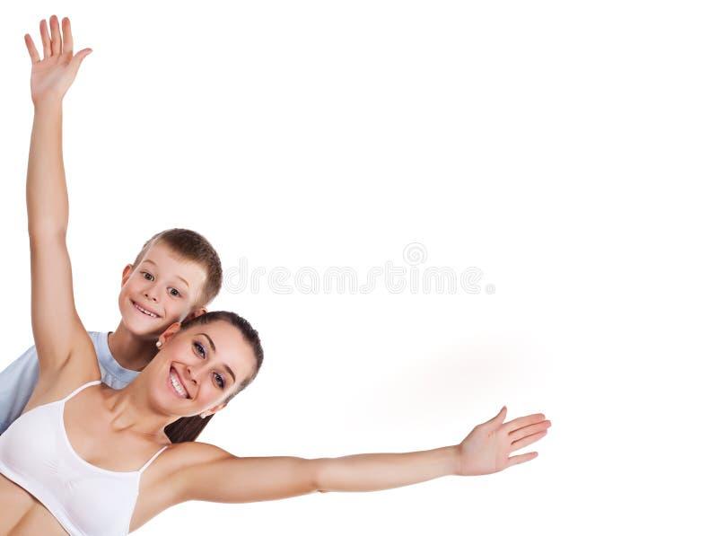 Den lyckliga modern och sonen gör övningar fotografering för bildbyråer
