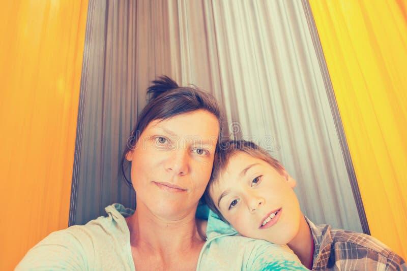 Den lyckliga modern och sonen vilar i en hängmatta och tar selfie arkivbilder