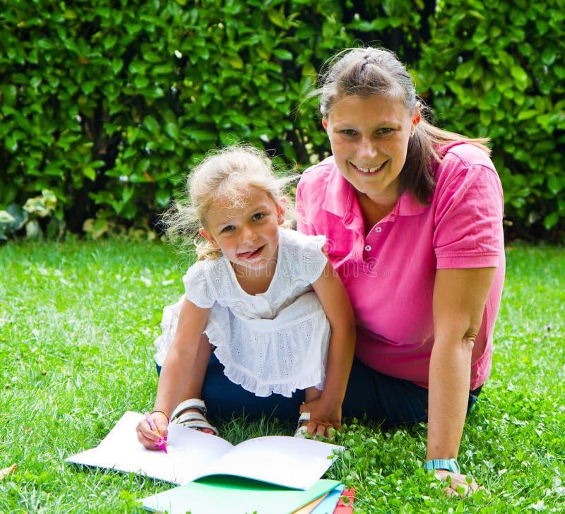Den lyckliga modern som drar en bok med, behandla som ett barn flickan arkivfoto