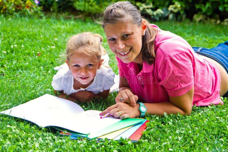 Den lyckliga modern som drar en bok med, behandla som ett barn flickan fotografering för bildbyråer