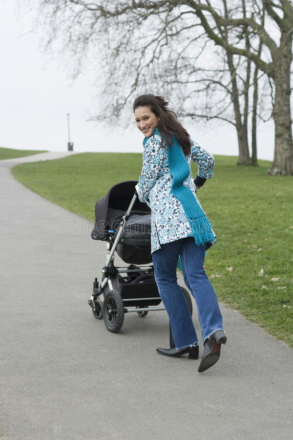 Den lyckliga modern som går med barnvagn parkerar in royaltyfri fotografi