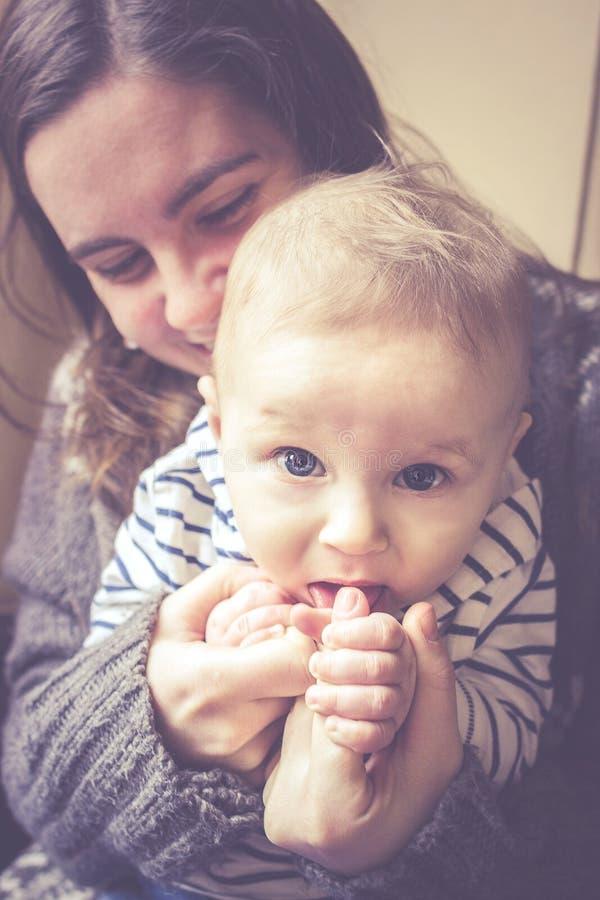 Den lyckliga modern som kramar hennes styggt, behandla som ett barn pojken arkivfoto