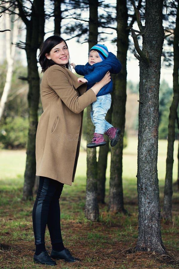 Den lyckliga modern som rymmer hennes lilla son i hennes armar i, parkerar flicka och pys i skogen royaltyfria foton