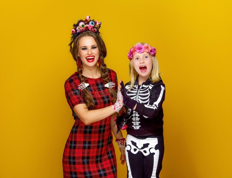 Den lyckliga moderna modern och barnet i halloween kostymerar höjdpunkt fem arkivbild