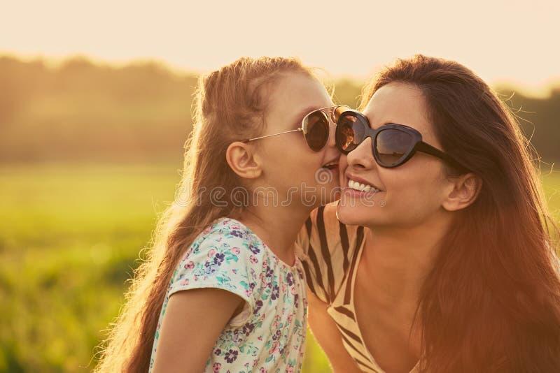 Den lyckliga modeungeflickan viskar hemligheten till hennes moder i öra i moderiktig solglasögon i profilsikt på natursolnedgångb fotografering för bildbyråer