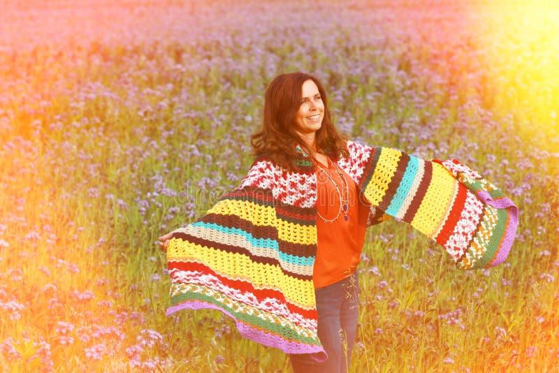 Den lyckliga mogna kvinnan i blommafält tycker om liv royaltyfria bilder