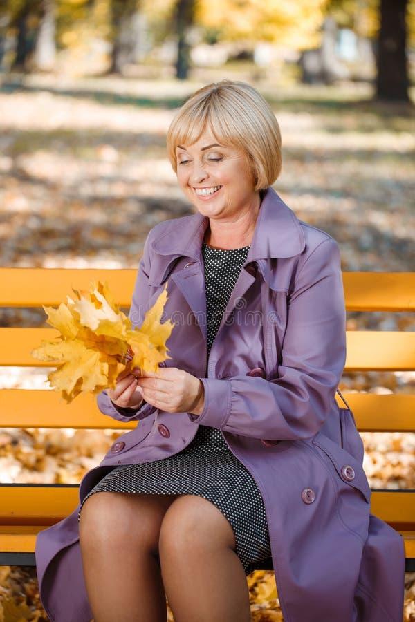 Den lyckliga mogna kvinnan sitter på en bänk i en parkera i höst royaltyfria foton