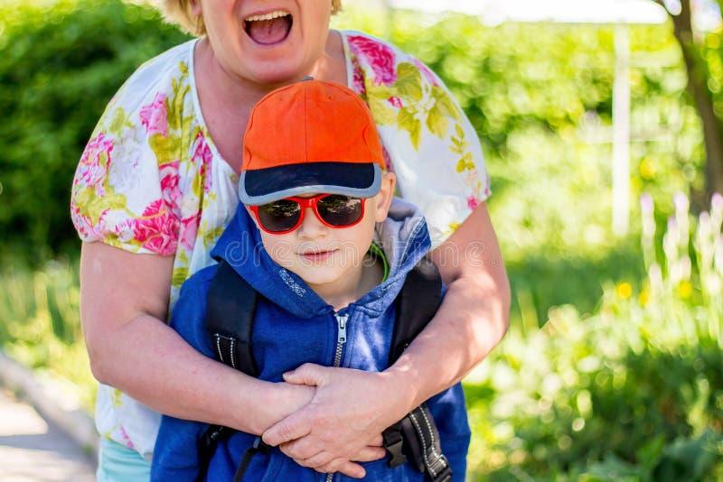 Den lyckliga mormodern omfamnade hennes sonson och skrattagyckel som jublar fotografering för bildbyråer