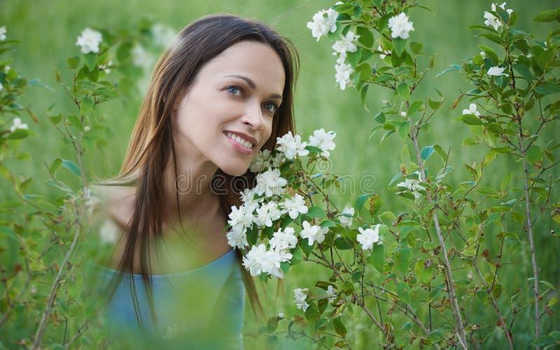 Den lyckliga nätta kvinnan sitter på ett gräs Sommardet friast?ende arkivbilder