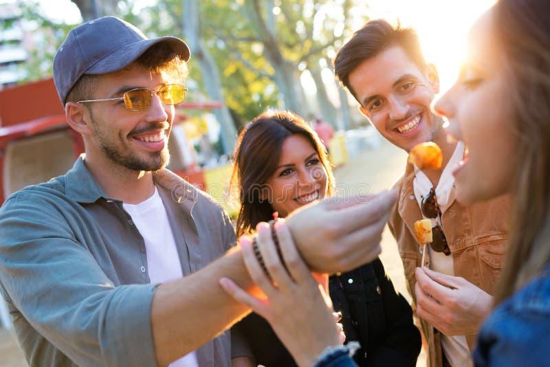 Den lyckliga och attraktiva unga gruppen av vänner som äter och delar snabbmat äter in, marknaden i gatan royaltyfri fotografi
