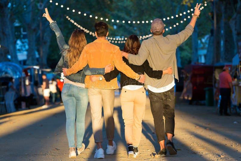 Den lyckliga och attraktiva unga gruppen av vänner som tycker om tid äter in, marknaden i gatan arkivbild