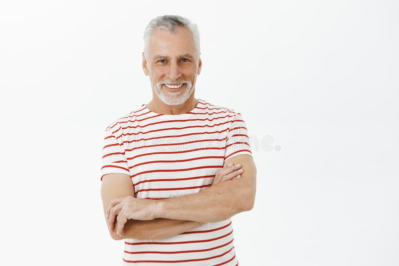 Den lyckliga och bekymmerslösa pensionerade höga mannen med det vita skägget och hår i den utsmyckade randiga t-skjortan som rymm arkivbild