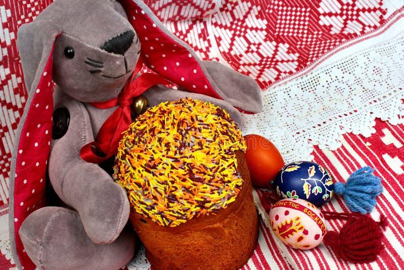 Den lyckliga påskkaninen, kakor och målade ägg med ordKristus har uppstiget i ryss royaltyfri bild