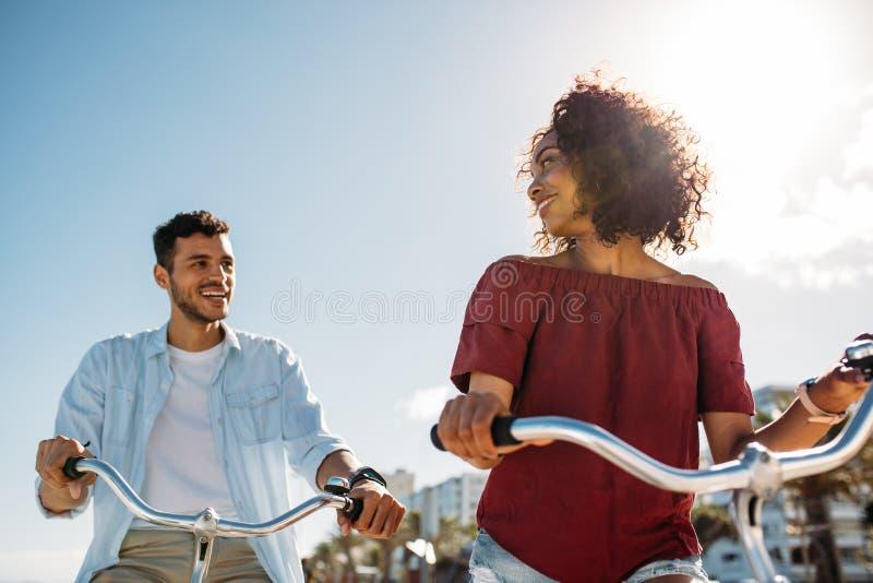 Den lyckliga parridningen cyklar i stad arkivfoton