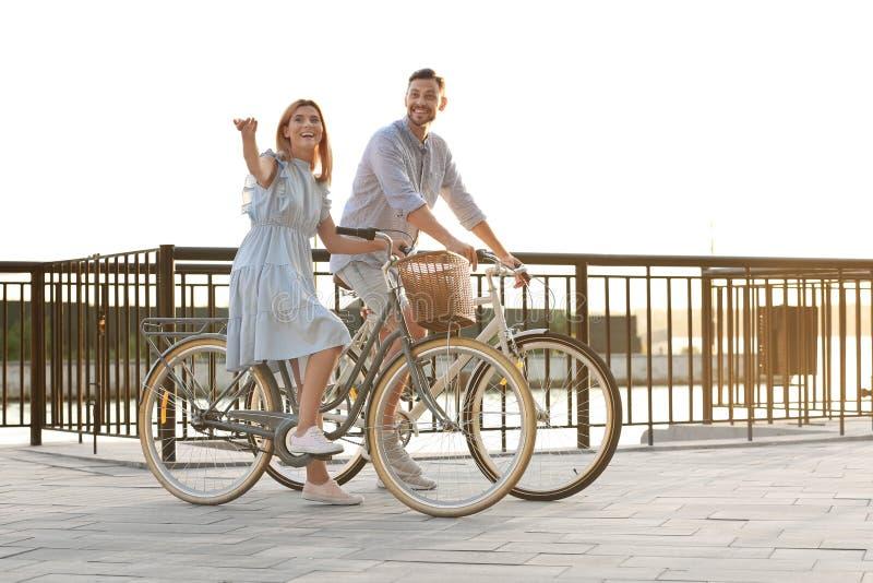 Den lyckliga parridningen cyklar utomhus arkivfoto