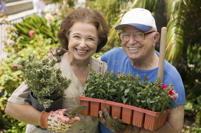 Den lyckliga pensionären kopplar ihop att arbeta i trädgården tillsammans fotografering för bildbyråer