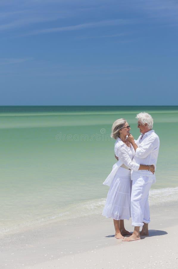 Den lyckliga pensionären kopplar ihop att omfamna på tropisk strand arkivbild