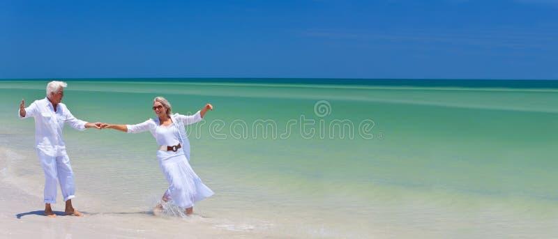 Den lyckliga pensionären kopplar ihop dansinnehav räcker på en tropisk strand royaltyfri bild
