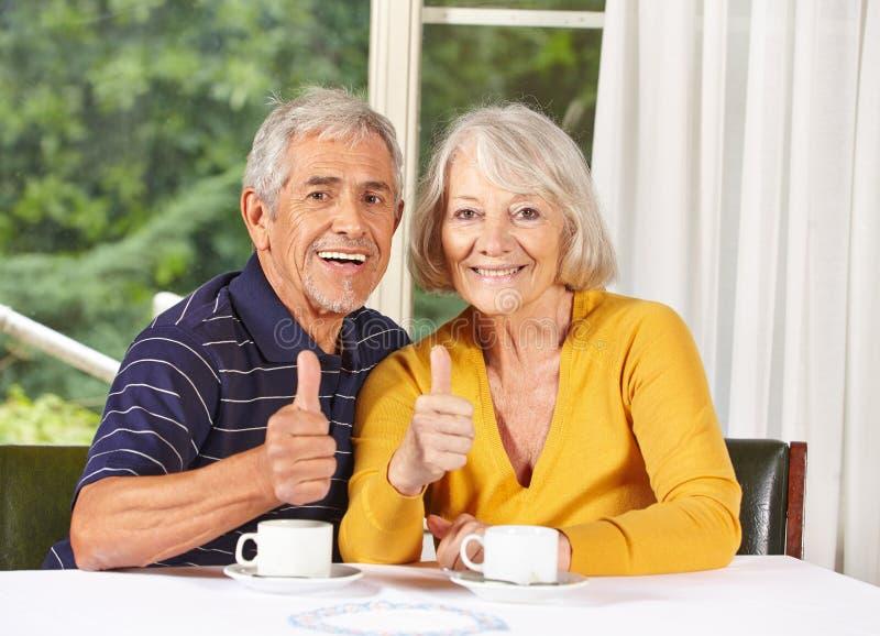 Den lyckliga pensionären kopplar ihop hållande tum royaltyfri fotografi