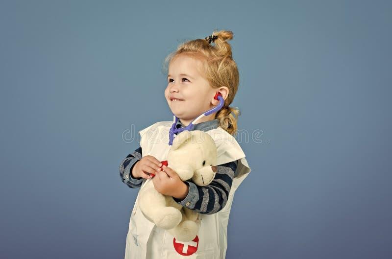 Den lyckliga pojken i doktorslikformig undersöker leksakhusdjuret med stetoskopet royaltyfri foto