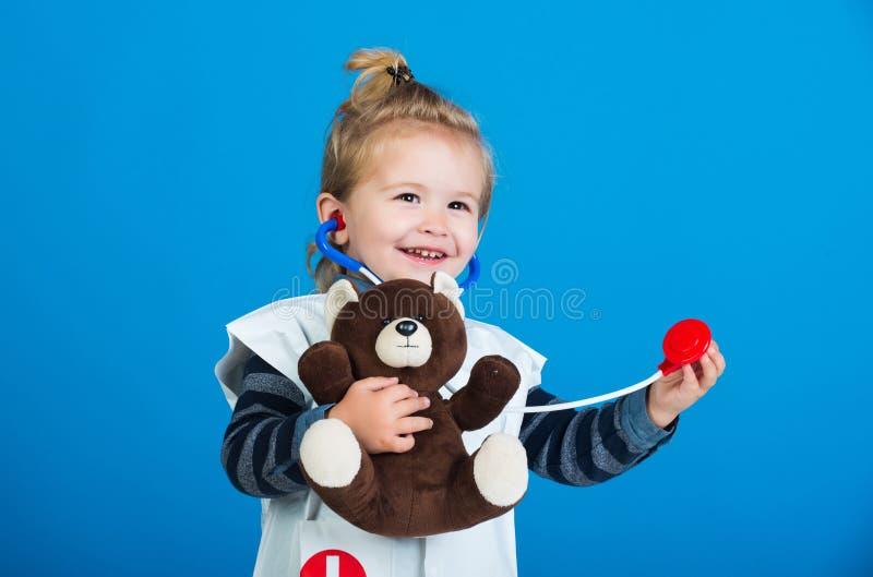 Den lyckliga pojken i doktorslikformig unders?ker leksakhusdjuret med stetoskopet royaltyfri bild