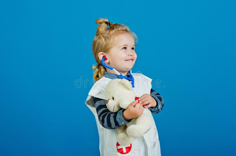 Den lyckliga pojken i doktorslikformig unders?ker leksakhusdjuret med stetoskopet royaltyfri foto