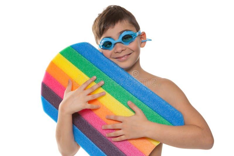 Den lyckliga pojken med exponeringsglas rymmer ett färgrikt simma bräde och leenden, begrepp, på en vit bakgrund royaltyfri fotografi
