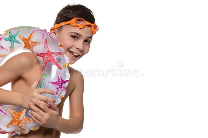 Den lyckliga pojken med orange simma skyddsglasögon och den uppblåsbara cirkeln, begrepp av semestern och vilar, på en vit bakgru royaltyfri bild