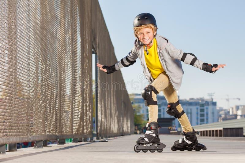 Den lyckliga pojken på rullar som gör trick på skridskon, parkerar royaltyfri fotografi