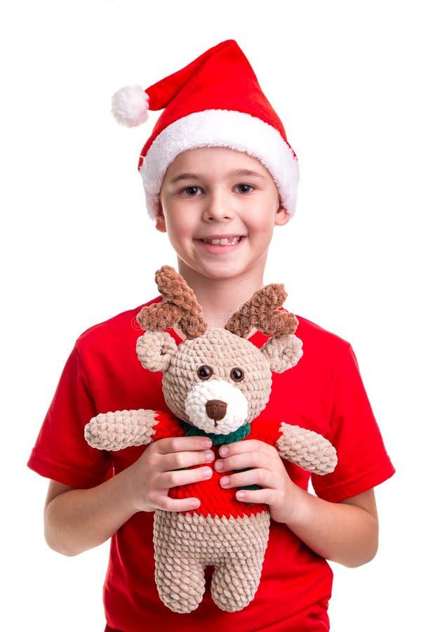 Den lyckliga pojken, den santa hatten på hans huvud, mottog den mjuka leksaken av hjortar Begrepp: jul eller ferie för lyckligt n arkivbild