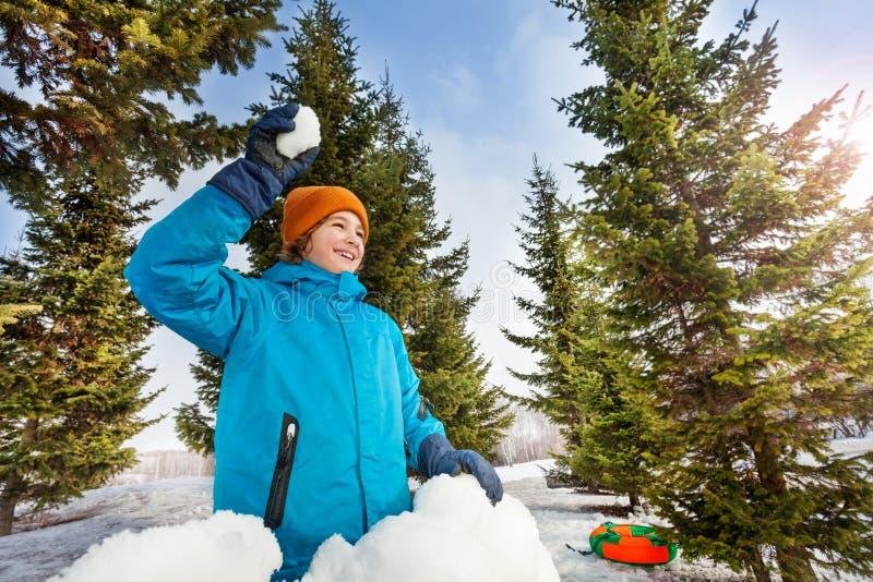 Den lyckliga pojken som är klar att kasta, kastar snöboll i skog arkivfoto