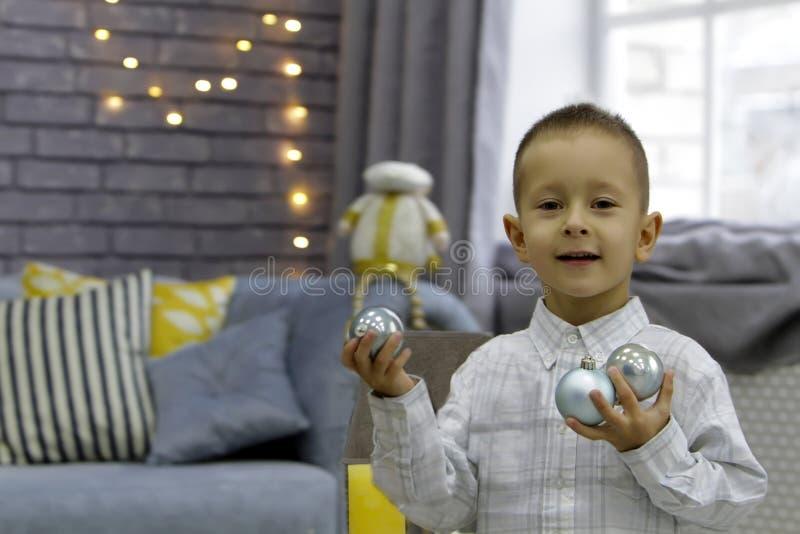 Den lyckliga pojken som står i ett stilfullt rum, rymmer bollar i båda händer på jul royaltyfri bild