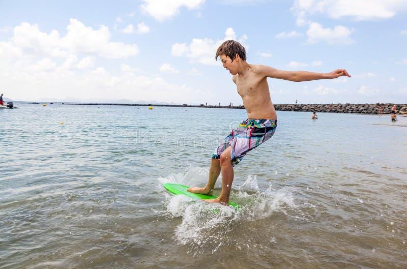 Download Den Lyckliga Pojken Tycker Om Att Surfa I Vågorna Arkivfoto - Bild av energi, utomhus: 37344276
